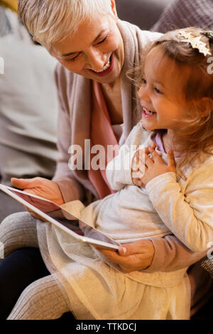 Happy grandmother looking at granddaughter while holding tablet computer at home - Stock Photo