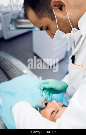 Dentist giving injection to patient at clinic - Stock Photo