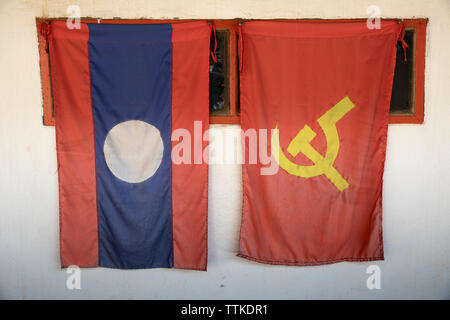 Laos national flag and the Lao People's Revolutionary Party (LPRP) flag hanging from shop window, Nong Khiaw, Muang Ngoi District, Luang Prabang Provi - Stock Photo