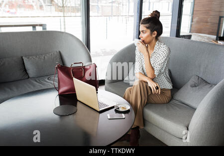 Thoughtful businesswoman drinking coffee while sitting on sofa at cafe - Stock Photo