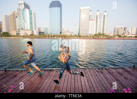 Man and woman running on wooden walkway by river against buildings - Stock Photo