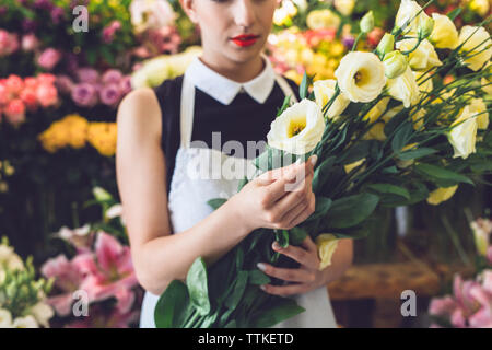 Midsection of florist holding roses in shop - Stock Photo