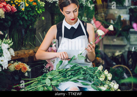 Female florist cutting stems of roses in flower shop - Stock Photo