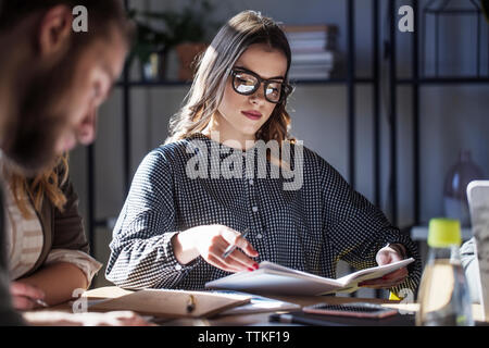 Woman studying while sitting with friends at table in classroom - Stock Photo
