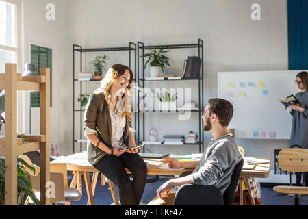 Smiling friends talking while sitting at desk in classroom - Stock Photo
