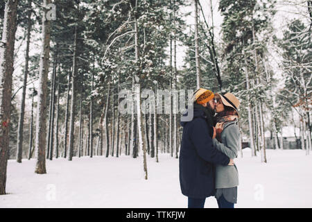 Romantic couple kissing while standing on snow covered field in forest - Stock Photo