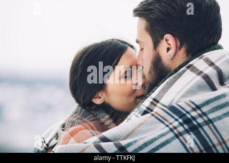Close-up of romantic couple wrapped in scarf - Stock Photo