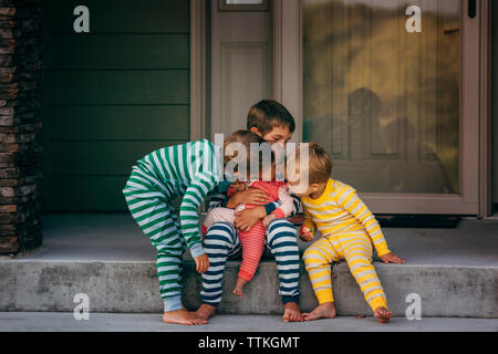 Loving brothers kissing sister in front of house - Stock Photo