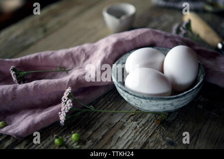 Close-up of eggs in bowl on wooden table - Stock Photo
