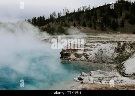 Smoke emitting from hot spring against mountain at Yellowstone National Park - Stock Photo