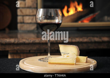 Close-up of wine with cheese slices served on wooden tray against fireplace - Stock Photo