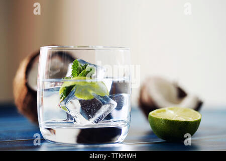Close-up of ice cubes in drink with fruits on table - Stock Photo