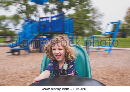Happy girl sitting in merry-go-round at playground - Stock Photo