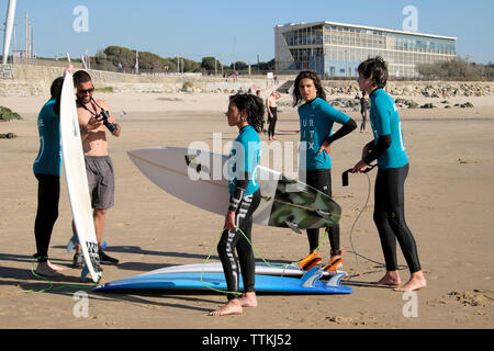 Boys surfers teens wearing wetsuits with surfboards stand and talk together on the beach at Matosinhos Porto Portugal Europe EU  KATHY DEWITT