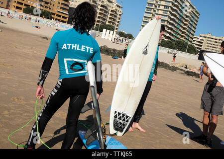 Boys surfers teens wearing wetsuits with surfboards stand and talk together on the beach at Matosinhos Porto in Portugal Europe EU  KATHY DEWITT
