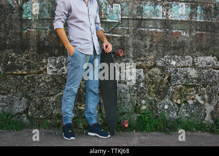 Low section of man holding skateboard while standing by wall - Stock Photo