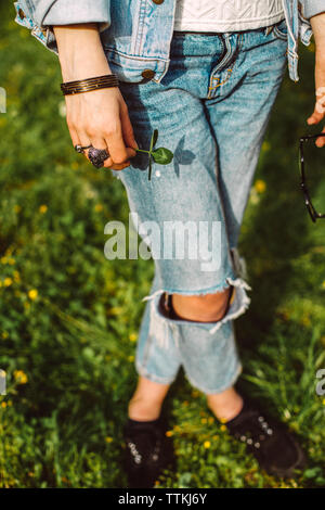 Low section of woman wearing torn jeans while standing on grassy field at park - Stock Photo