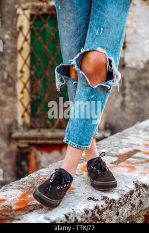 Low section of woman wearing torn jeans while standing on retaining wall - Stock Photo