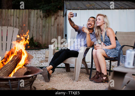 Friends taking selfie while sitting on chairs at yard - Stock Photo