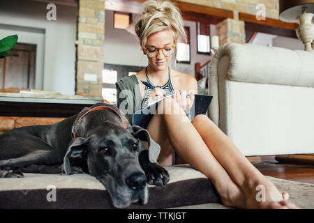 Woman writing diary while sitting by Great Dane on pet bed at home - Stock Photo