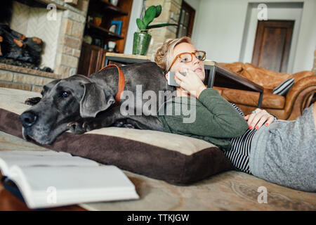 Woman talking on smart phone while lying on Great Dane at home - Stock Photo