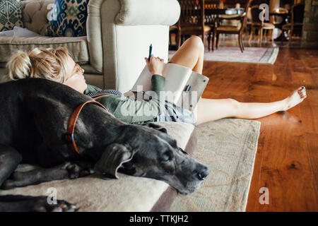 Woman writing diary while reclining on Great Dane - Stock Photo