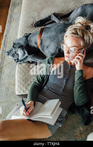 Overhead view of woman talking with diary using smart phone while relaxing on Great Dane at home - Stock Photo