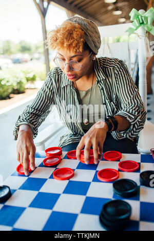 Woman playing checkers while sitting at yard - Stock Photo
