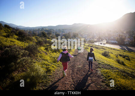 Rear view of sibling running on road against mountains in sunny day - Stock Photo