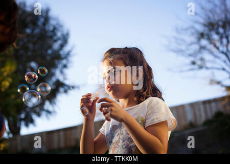 Low angle view of girl making bubbles against sky - Stock Photo