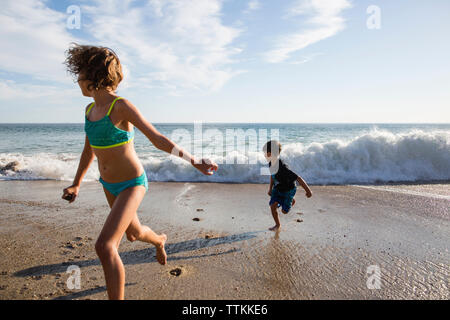 Girl and boy running from rushing waves at beach - Stock Photo