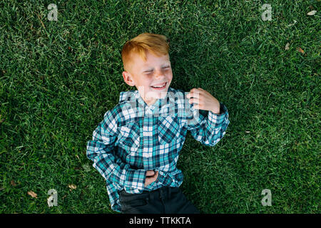 Overhead view of happy boy lying on grassy field at park - Stock Photo