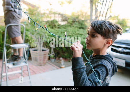 Son assisting father in hanging colorful string lights during Christmas - Stock Photo