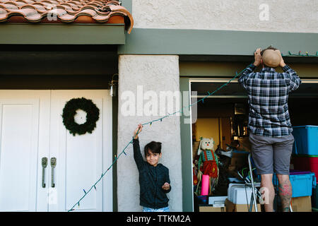 Portrait of son assisting father in hanging colorful string lights on wall during Christmas - Stock Photo