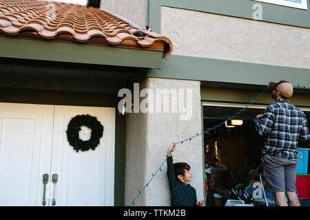 Son looking at father hanging colorful string lights on wall during Christmas - Stock Photo