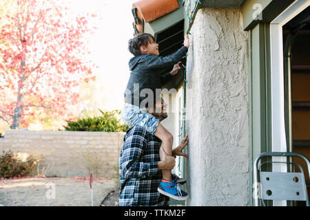 Side view of father carrying son on shoulders hanging string lights on wall during Christmas - Stock Photo