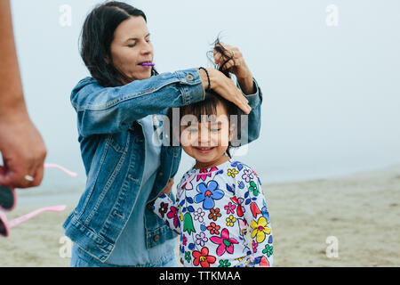 Mother Puts Toddler Daughter's Hair up At Beach - Stock Photo