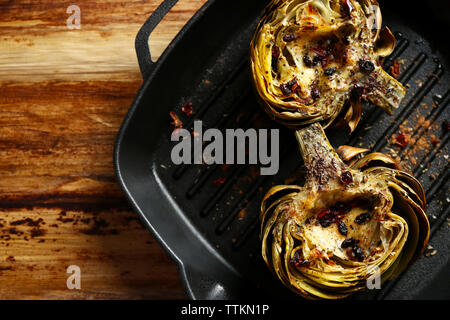 Baked artichokes in black grill pan on wooden background - Stock Photo