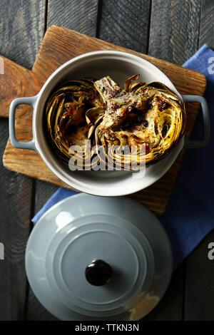 Baked artichokes in saucepan on cutting board - Stock Photo