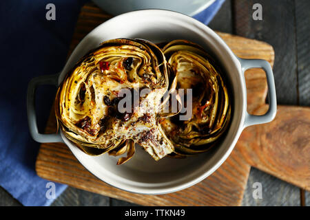 Baked artichokes in saucepan on cutting board, close up - Stock Photo