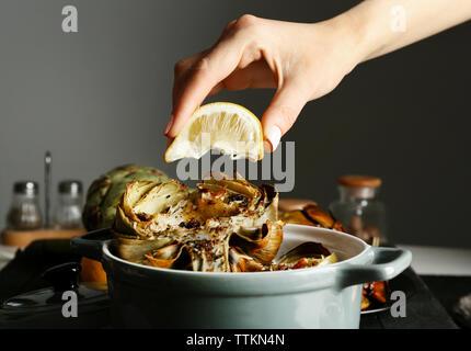 Female hand squeezing lemon on baked artichokes in saucepan - Stock Photo