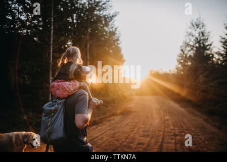 Rear view of father carrying daughter on shoulders while walking with dog on dirt road - Stock Photo