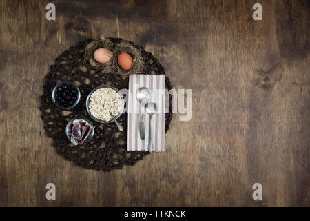 Overhead view of breakfast cereal with fruits and eggs on plate mat over wooden table - Stock Photo