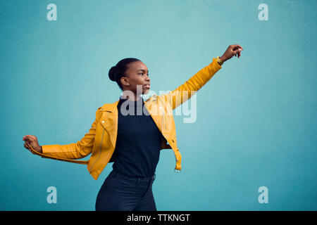 Confident fashion model standing with arms outstretched against blue wall - Stock Photo