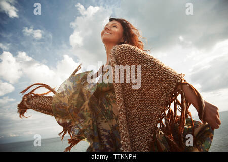 Low angle view of happy woman dancing by sea against cloudy sky - Stock Photo