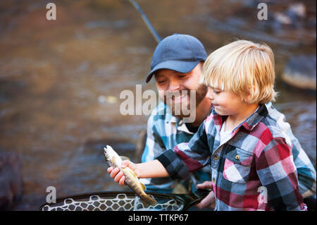 Smiling father looking at boy putting fish in net against river - Stock Photo