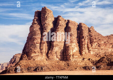 The rock formation known as 'The Seven Pillars of Wisdom' in the Jordanian desert at Wadi Rum or Valley of the Moon. - Stock Photo