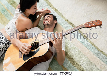 Overhead view of cheerful man playing guitar while lying on rug with woman - Stock Photo