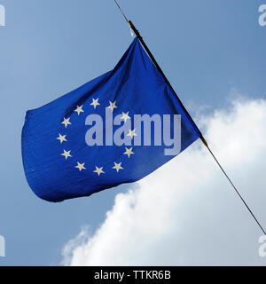 A flag of european union is flying on a background of blue sky with white clouds - Stock Photo