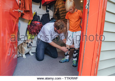 Dog sitting by father assisting son in wearing shin guards at home seen through doorway - Stock Photo